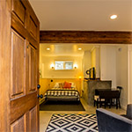 Eco-Studio: Looking through the entryway to the double bed, television, and dining area.